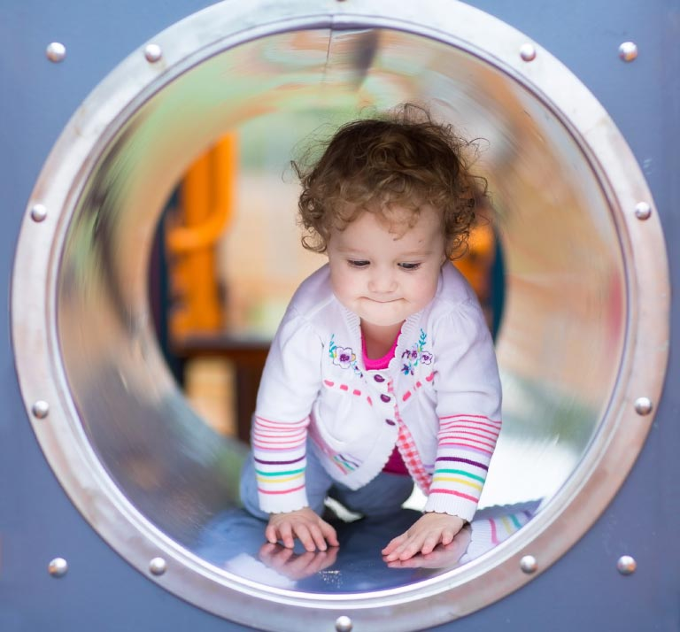Cute curly baby girl climbing slide on playground