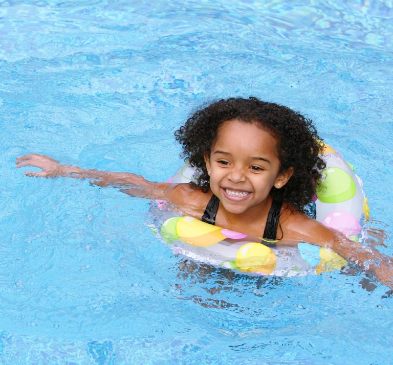 Young girl in swimming pool with colored floating ring