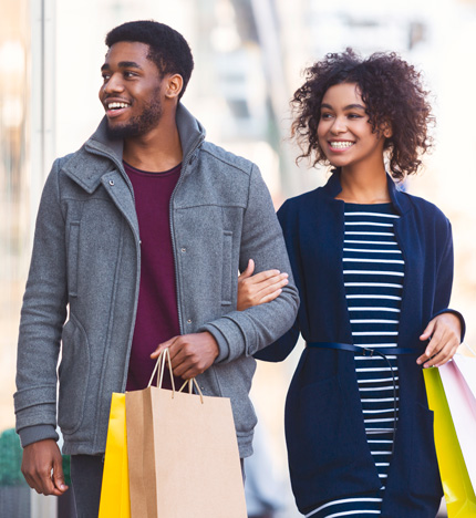 couple holding shopping bags and walking