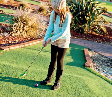 girl about to putt a golfball