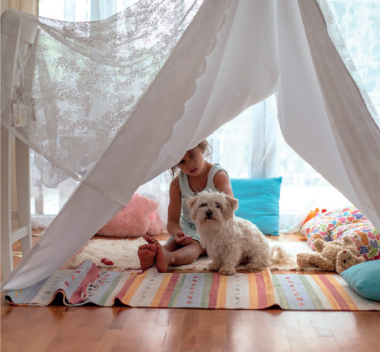 girl and dog in a blanket fort
