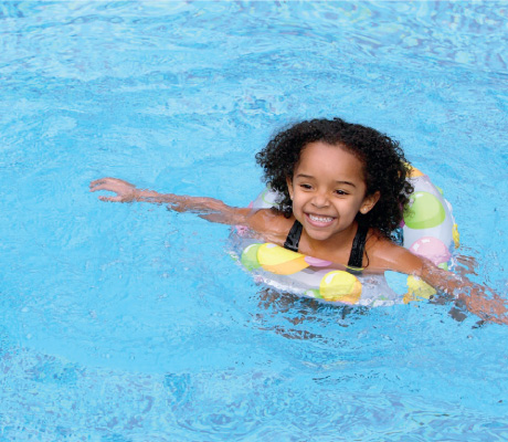 girl swimming in a pool with an inflatable