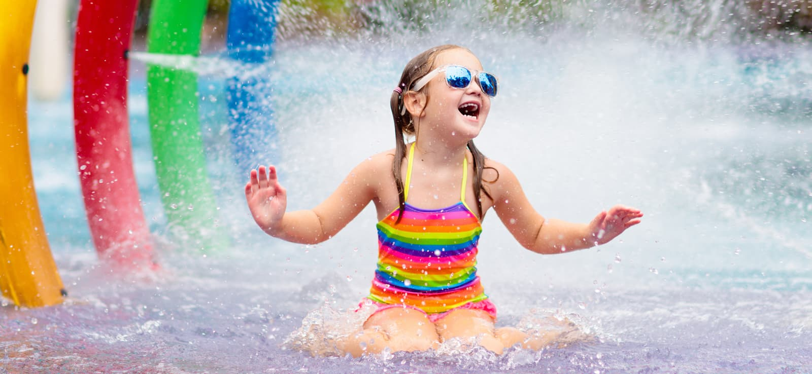 girl wearing sunglasses getting splashed at waterpark
