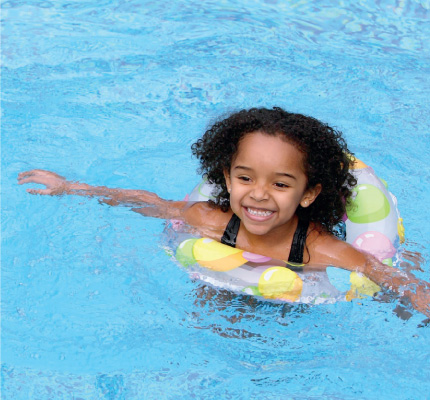 girl with a flotation device swimming in a pool