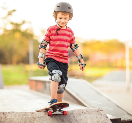 kid skateboarding on a ramp with protective gear on